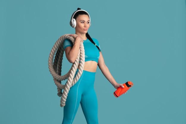 Schöner junger weiblicher athlet, der auf monochromem porträt der blauen wand übt