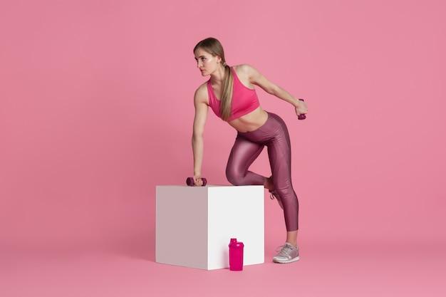Schöner junger weiblicher athlet, der auf monochromem porträt der rosa studiowand übt