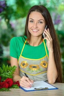 Schöner junger weiblicher florist, der am telefon nimmt.