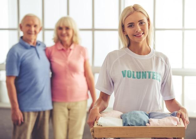 Schöner junger weiblicher freiwilliger hält einen kasten.