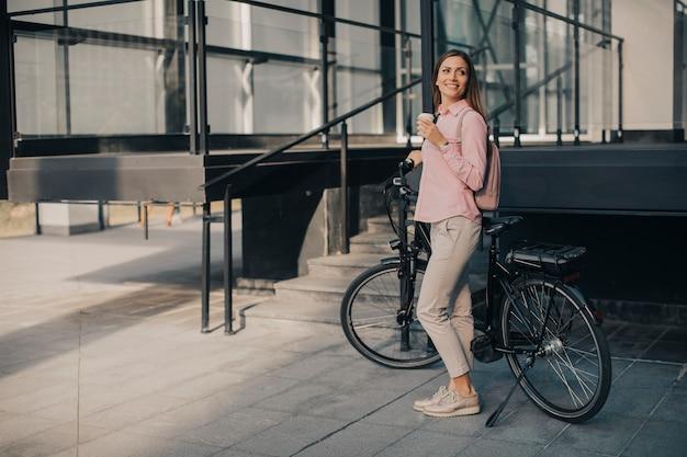 Schöner junger weiblicher radfahrer trinkt warmen kaffee von einer schale durch das elektrische fahrrad in der städtischen umwelt