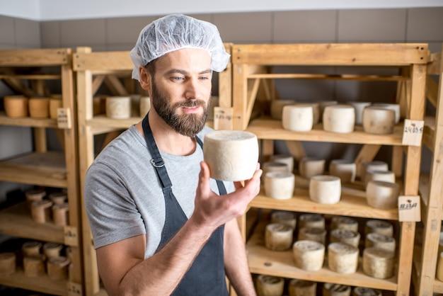 Schöner käser, der den alterungsprozess des ziegenkäses im kleinen keller überprüft