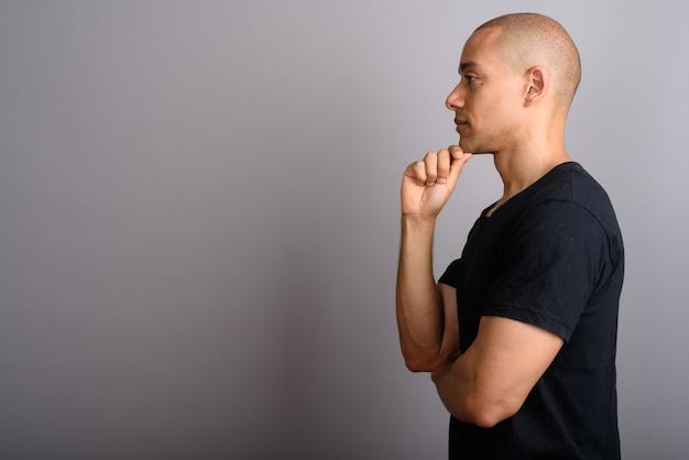 Schöner kahler mann, der schwarzes hemd auf grau trägt