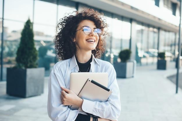 Schöner kaukasischer geschäftsmann mit lockigem haar, das draußen mit einer tablette und einem laptop aufwirft, während brillen an einem sonnigen tag tragen