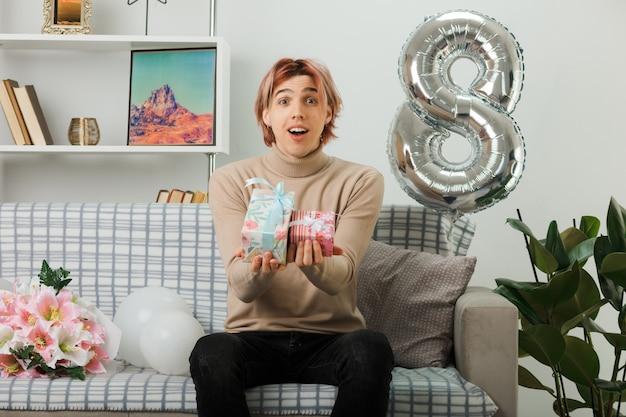 Schöner kerl am glücklichen frauentag, der auf dem sofa im wohnzimmer ein geschenk vor der kamera hält
