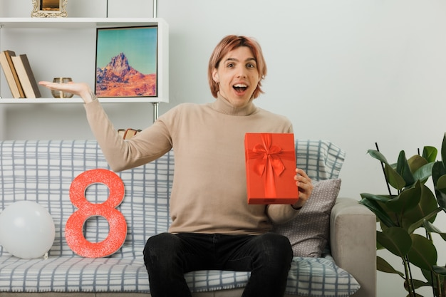 Schöner kerl am glücklichen frauentag, der das geschenk auf dem sofa im wohnzimmer hält