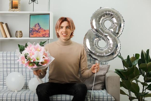 Schöner kerl am glücklichen frauentag, der den ballon nummer acht und den blumenstrauß hält, der auf dem sofa im wohnzimmer sitzt