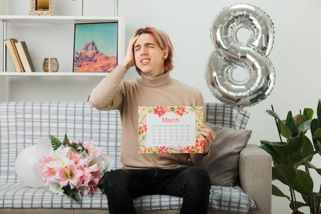Schöner kerl am glücklichen frauentag, der den kalender auf dem sofa im wohnzimmer hält
