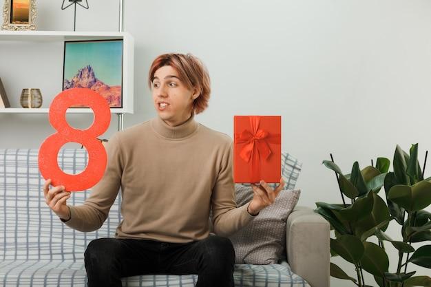 Schöner kerl am glücklichen frauentag, der die nummer acht mit geschenk auf dem sofa im wohnzimmer hält