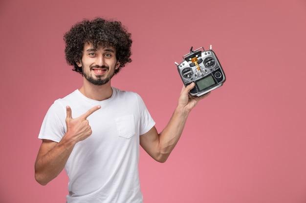Schöner kerl der vorderansicht, der auf seinen funkcontroller des elektronischen roboters hinweist