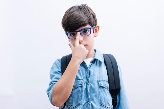 Schöner kinderjunge student mit brille und rucksack, der bücher auf lokalisiertem weißem hintergrund hält