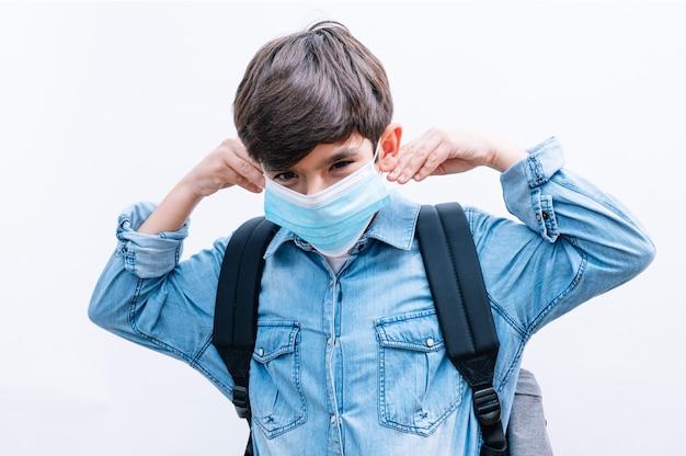 Schöner kinderjunge student mit rucksack und maske, die bücher auf weißem hintergrund halten