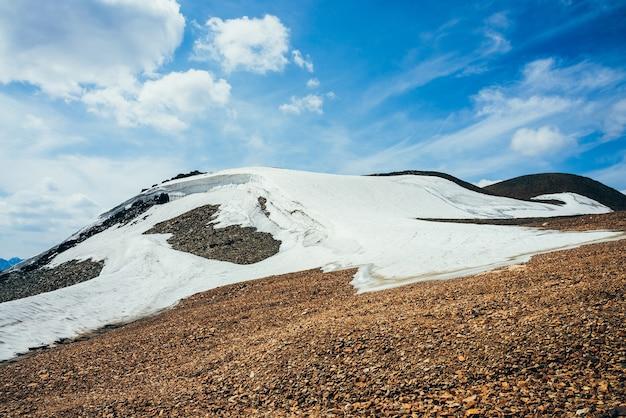Schöner kleiner gletscher mit eisgesims auf steinigem hügel unter bewölktem himmel. schnee am berg.