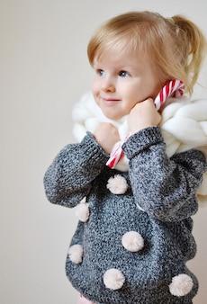 Schöner kleiner glücklicher blonder ginger girl giant knitted scarf mit stern-weihnachtskonzept-dekor des neuen jahres