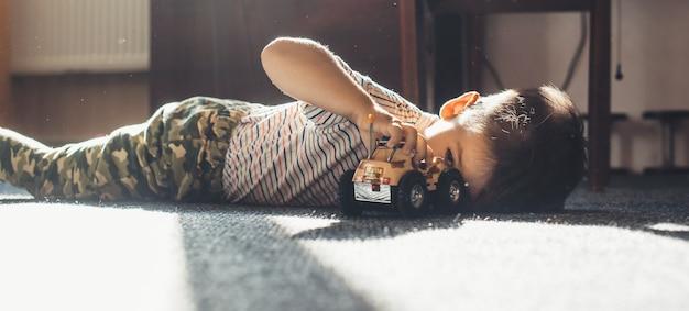 Schöner kleiner junge, der an einem sonnigen tag auf dem boden mit einem spielzeugauto spielt