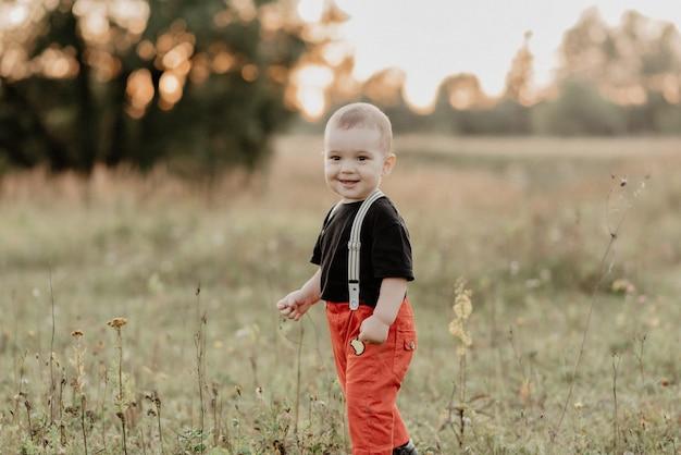 Schöner kleiner junge, der das gehen auf gras lächelt