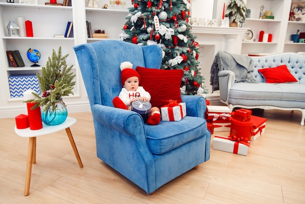 Schöner kleiner junge in der weihnachtskleidung sitzt im blauen großen stuhl und hält geschenkbox in seinen händen.