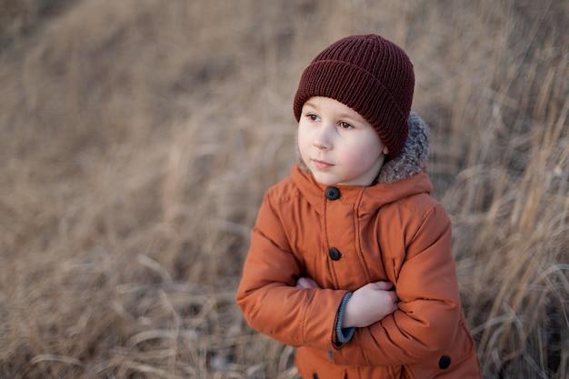 Schöner kleiner junge in jacke und hut draußen