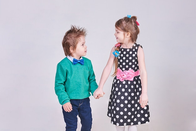 Schöner kleiner junge und mädchen halten händchen und schauen sich an