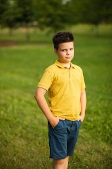 Schöner kleiner kaukasischer junge mit dunklem haar in gelbem t-shirt und blauen shorts, der seine hände in den taschen hält und lächelt