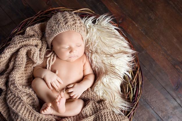 Schöner kleiner neugeborener 20 tage schläft in einem korb mit gestricktem plaid. porträt eines hübschen neugeborenen jungen