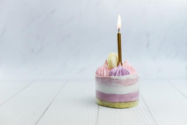 Schöner kleiner rosa kuchen mit sahne mit einer kerze