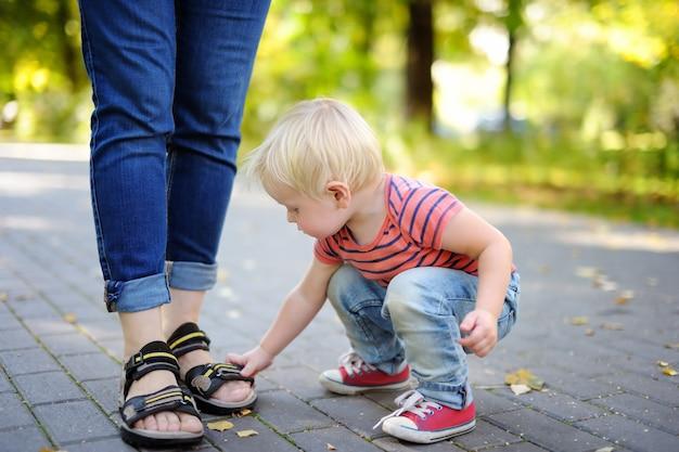 Schöner kleinkindjunge, der mit schuhen am sonnigen park spielt