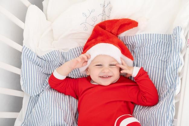 Schöner kleinkindjunge in der weihnachtsmütze, roter anzug, der im kinderbett zu hause lächelt.