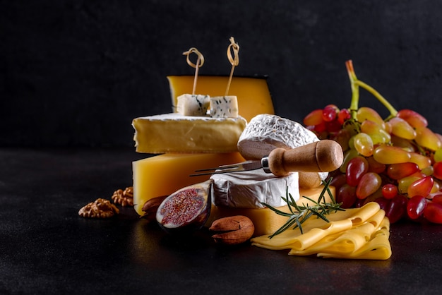 Schöner köstlicher camembertkäse, parmesan, brie mit trauben und feigen auf einem holzbrett. snacks für wein im urlaub