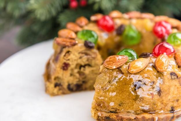 Schöner köstlicher selbst gemachter weihnachtsfruchtkuchen auf weißer servierplatte