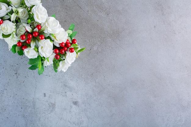 Schöner kranz mit weißen rosenblüten auf grau