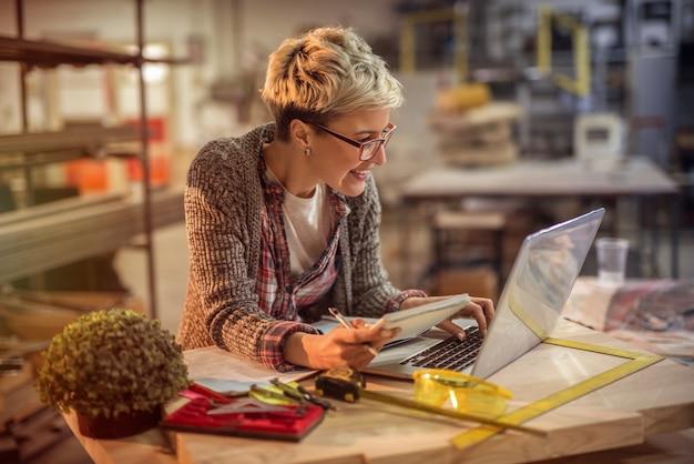 Schöner kreativer junger weiblicher ingenieur, der an laptop in ihren werkstätten arbeitet