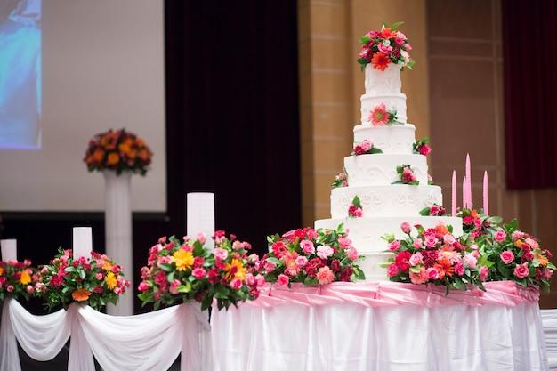 Schöner kuchen dekorieren mit rosa rosenblüte und kerze für die hochzeitszeremonie