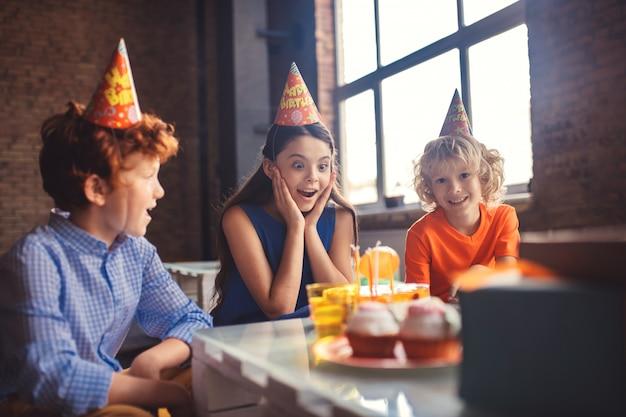 Schöner kuchen. drei kinder, die den kuchen betrachten und aufgeregt schauen