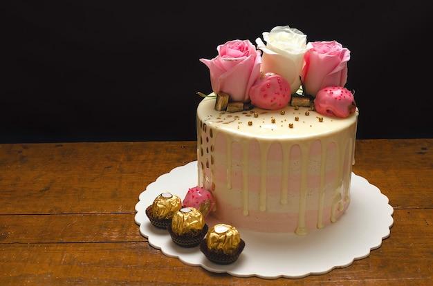 Schöner kuchen verziert mit natürlichen rosen und pralinen auf holztisch