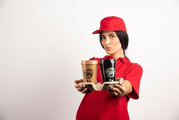 Schöner kurier, der kaffee zum mitnehmen hält. hochwertiges foto