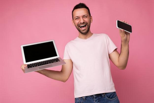 Schöner lachender mann, der laptop-computer und mobiltelefon hält und die kamera im t-shirt auf isoliertem rosa hintergrund anschaut