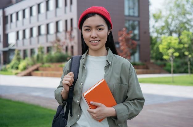 Schöner lächelnder asiatischer student, der ein buch hält, das die kamera zurück zum schulbildungskonzept betrachtet