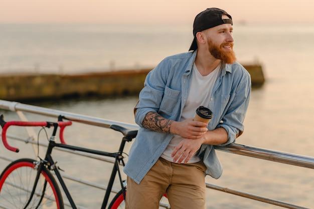 Schöner lächelnder bärtiger hipsterart-ingwer-bärtiger mann, der jeanshemd und -kappe mit fahrrad im morgensonnenaufgang durch das meer trinkt kaffee, gesunder reisender des aktiven lebensstils trägt