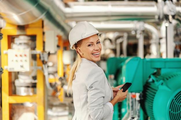 Schöner lächelnder blonder weiblicher ceo im anzug mit helm auf kopf, der über schulter und sms-nachricht beim stehen im heizwerk schaut.