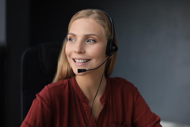 Schöner lächelnder call-center-mitarbeiter mit kopfhörern arbeitet isoliert auf grauem hintergrund.