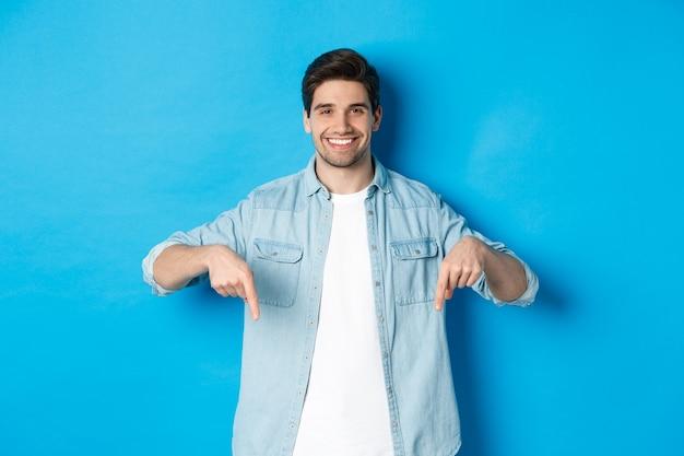 Schöner lächelnder erwachsener mann führt produkt ein, zeigt mit den fingern nach unten auf die förderung und steht vor blauem hintergrund.