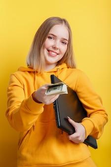 Schöner lächelnder freiberufler der jungen frau mit laptop nehmen dollargeldbanknoten. it-remote-freelancer-remote-mitarbeiter über laptop isoliert über gelbem farbhintergrund.