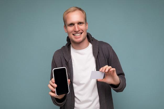 Schöner lächelnder glücklicher mann, der alltagskleidung trägt, isoliert auf der hintergrundwand, die telefon und kreditkarte hält und die zahlung mit blick auf die kamera macht