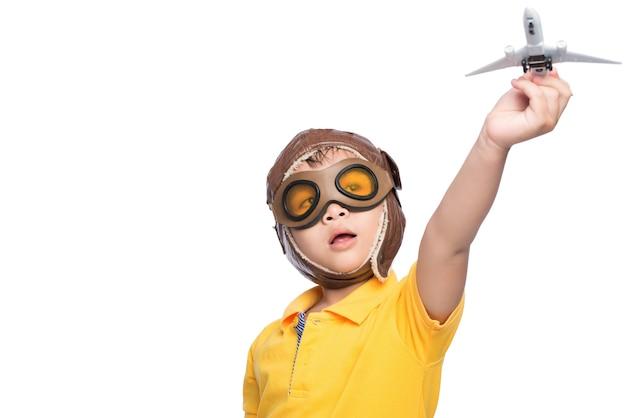 Schöner lächelnder kinderjunge im helm auf einem weißen hintergrund, der mit einem flugzeug spielt.