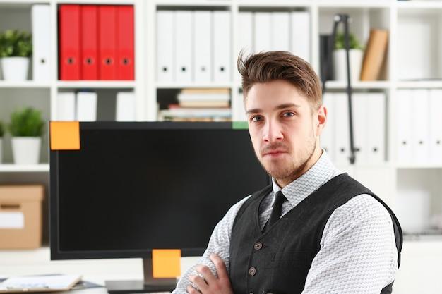 Schöner lächelnder mann in anzug und krawatte steht im büro