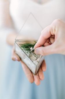 Schöner lächelnder meister der hochzeitszeremonie, der glasbox mit eheringen hält