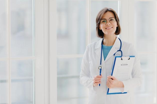 Schöner lächelnder praktikant hält zwischenablage mit geschriebenen papieren und stift, trägt weiße uniform