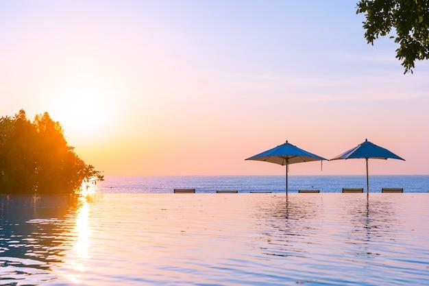 Schöner landschaftsaußenpool mit regenschirm und klappstuhl im hotelerholungsort für entspannen sich tra