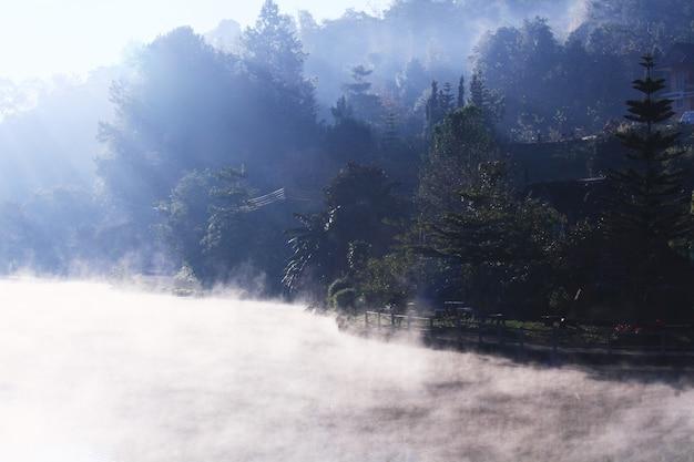 Schöner landschaftshimmel des nebels und des nebels über dem see und dem sonnenaufgang, die mit reflexion des blauen himmels auf der wasseroberfläche am bergstammdorf auf berg in thailand glänzen